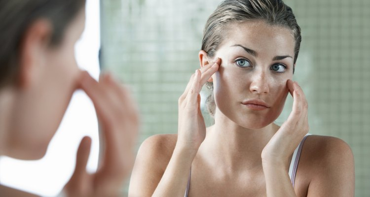 Woman Examining Herself In Front Of Mirror
