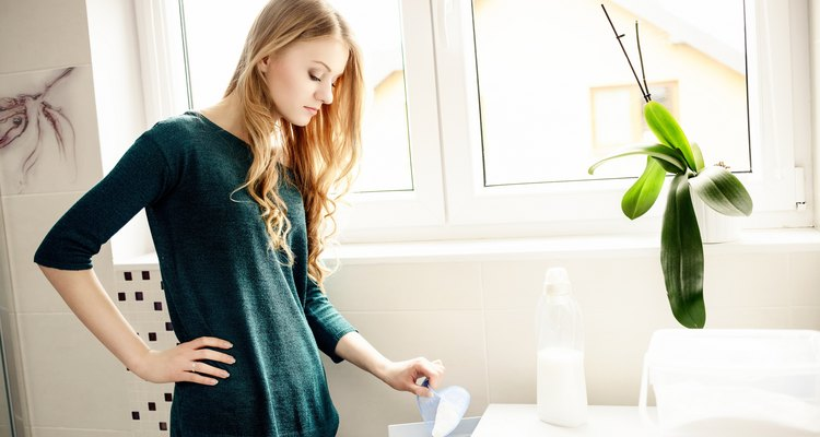 Young blond woman pouring washing powder