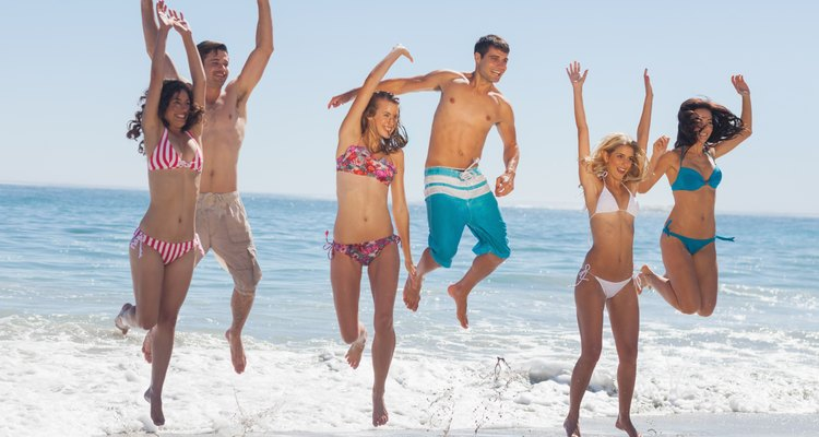 Happy friends jumping on the beach