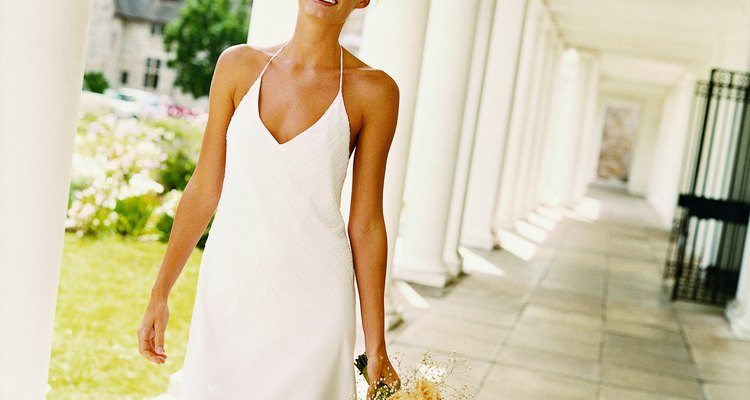 Smiling Bride Standing in the Arcade of a formal Garden Holding a Bouquet of White Roses