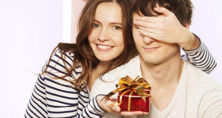 Chica sosteniendo un regalo para un hombre joven.