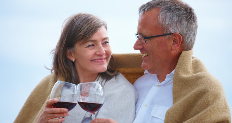 Close-up of romantic senior couple holding wineglasses on the beach