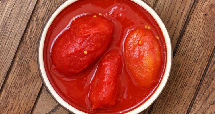 Whole canned tomatoes in pottery dish from above on wood.