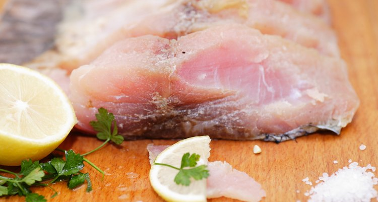Fresh white fish fillets on chopping board