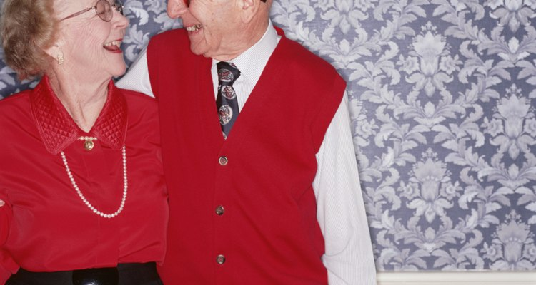 Senior couple standing together laughing, indoors, portrait