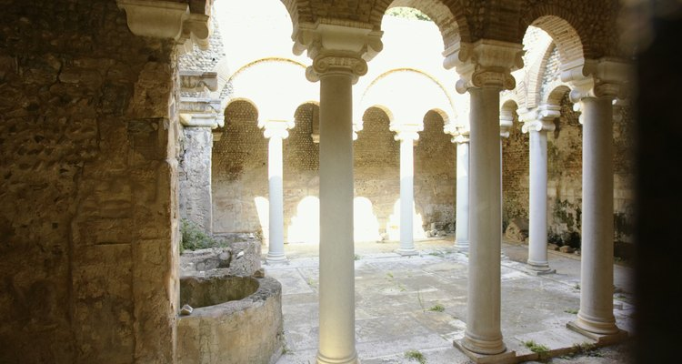 La luz del sol brilla a través de ruinas griegas.