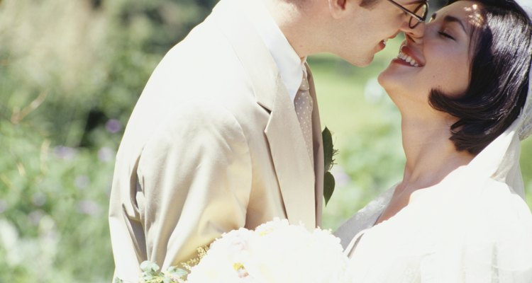Bride and groom kissing in park, close-up
