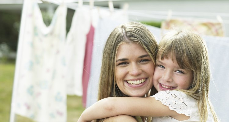 Mother and daughter (4-5) hugging by laundry line, portrait