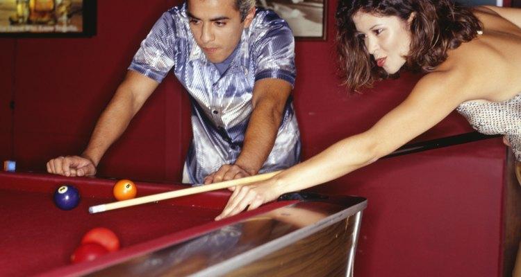 Casal jogando bilhar na sala de jogos