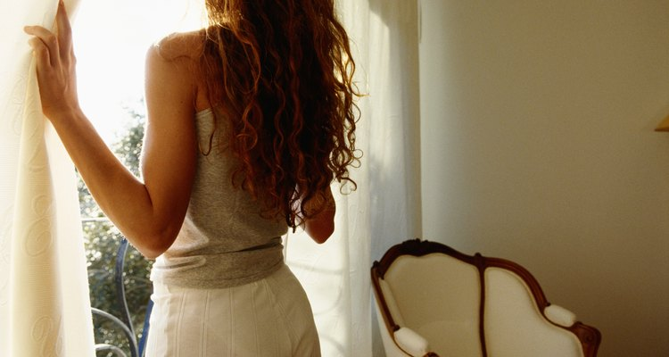 Young woman holding curtain, looking out window, rear view