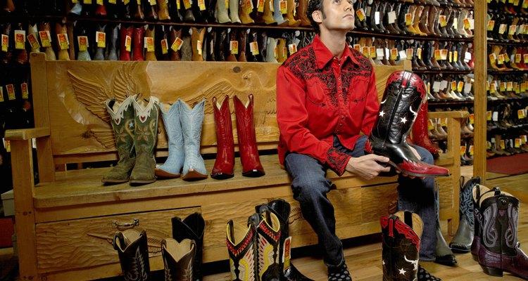 Hombre joven probándose diferentes botas de vaquero.