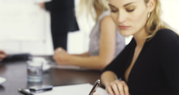 Young businesswoman writing in meeting