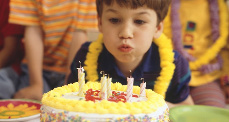 Boy at party, blowing out birthday candles