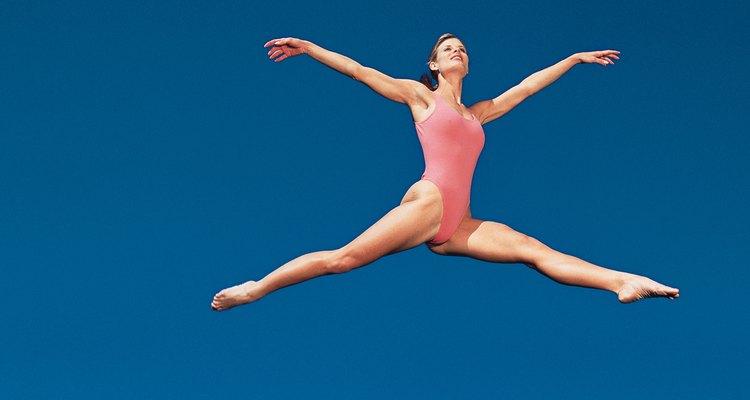 Woman in leotard leaping across sky