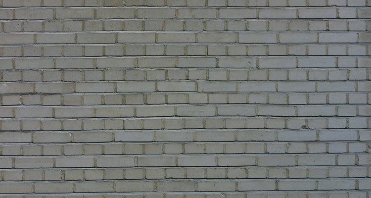 Como remover respingos de cimento em uma parede de tijolos