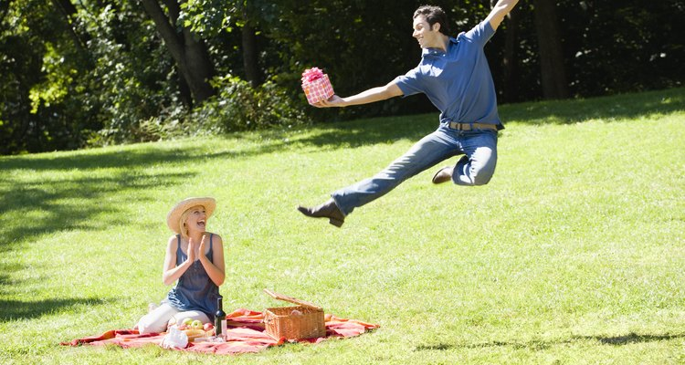 Man giving woman present at picnic in park