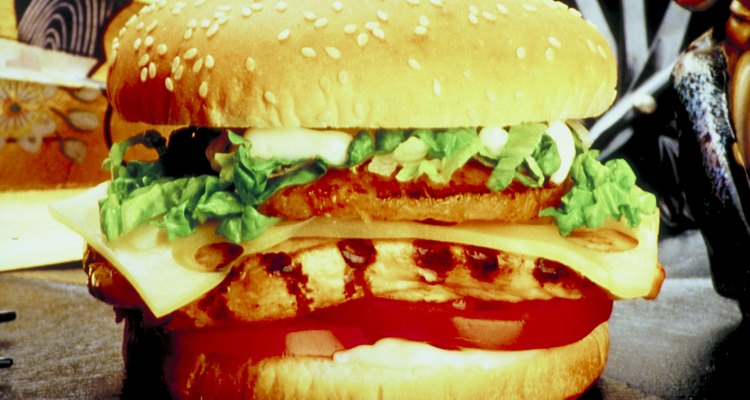 Espera 1 minuto, da vuelta las hamburguesas, y añade otra pizca de condimento.
