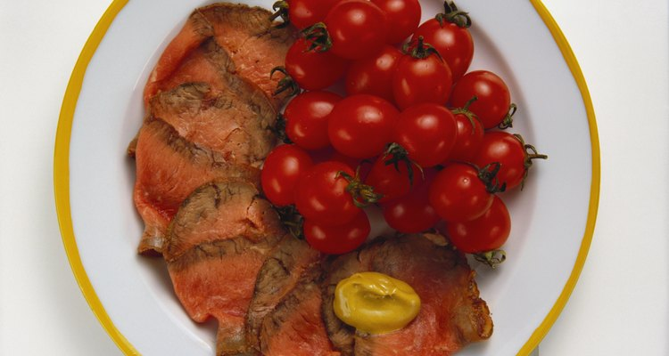 Slices of medium-rare roast beef shingled on a white plate with a side of fresh cherry tomatoes.
