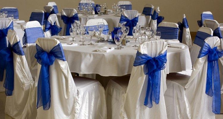 La decoración incluye moños azules de tul amarrados sobre el cubresillas blanco.