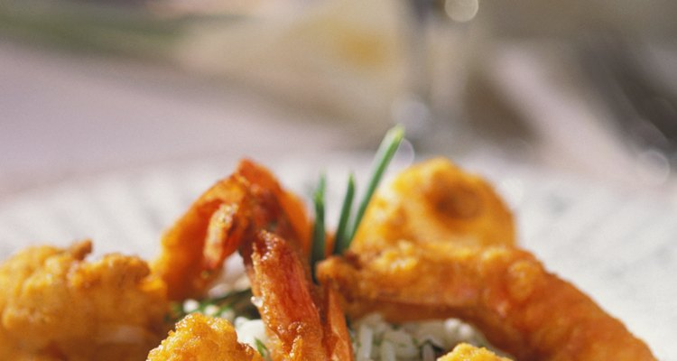 Plate with fried shrimp and rice, with wineglass in background, close-up