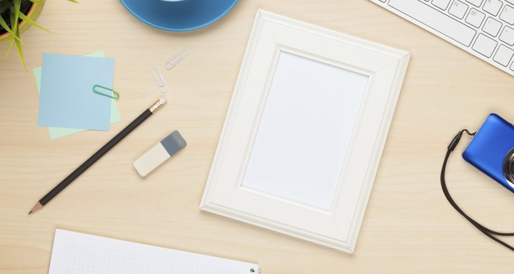 Photo frame on office table with notepad, computer and camera