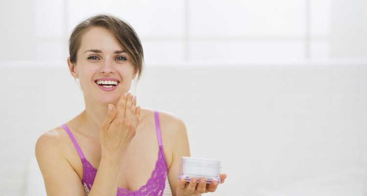 healthy woman applying creme on face in bedroom