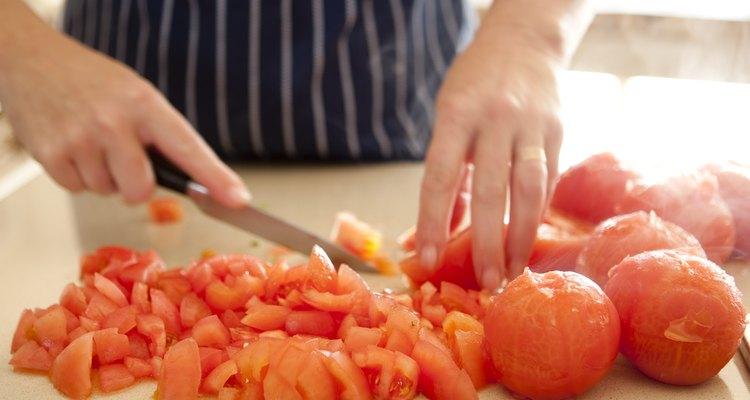Miembros del personal de cocina preparan los alimentos antes de cocinarlos.
