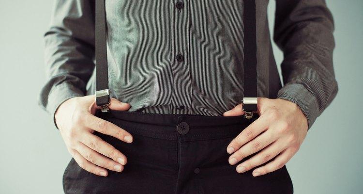 Men's hands holding pants with suspenders