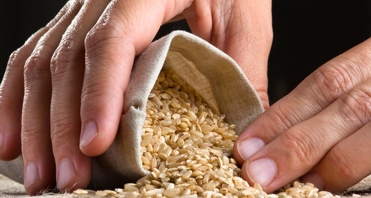 hand with brown rice in linen sack