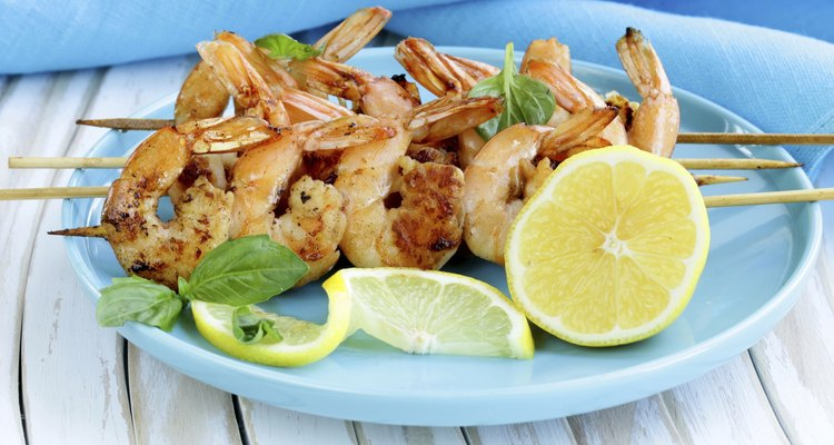 shrimp grilled on wooden skewers with lemon and basil