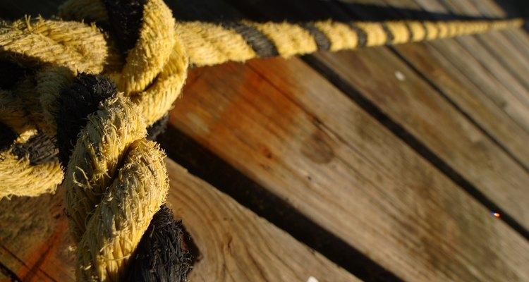 Desliza el trozo de cuerda a través del agujero en un extremo del tablón, asegúralo al tablón y a la cuerda de soporte principal.