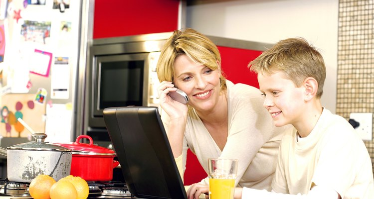 Mother talking on cell phone in kitchen with son