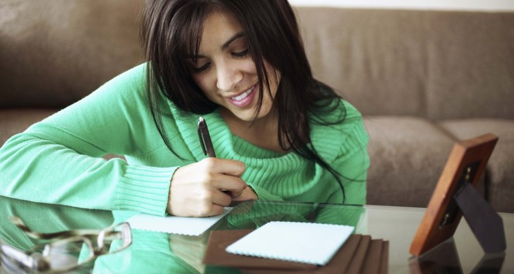 Woman writing note on coffee table