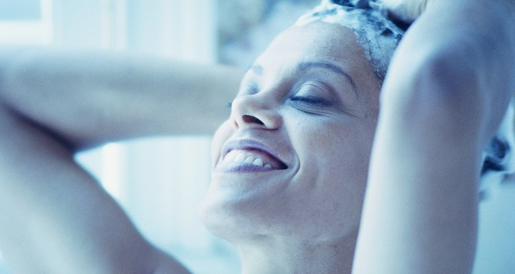 Woman shampooing hair and smiling