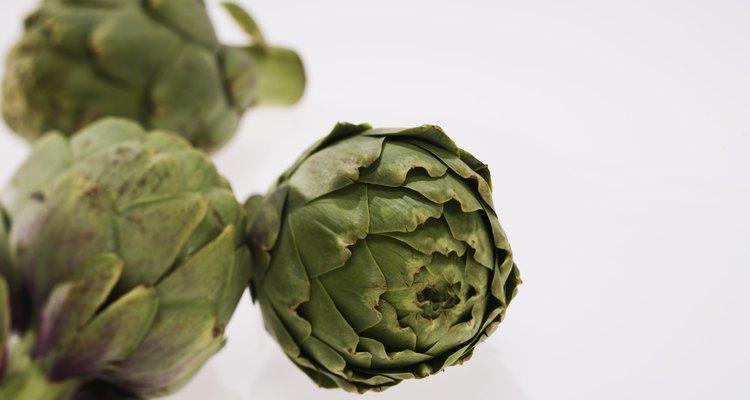 Coloca una alcachofa en el centro de una disposición de frutas frescas para una pieza central vibrante.