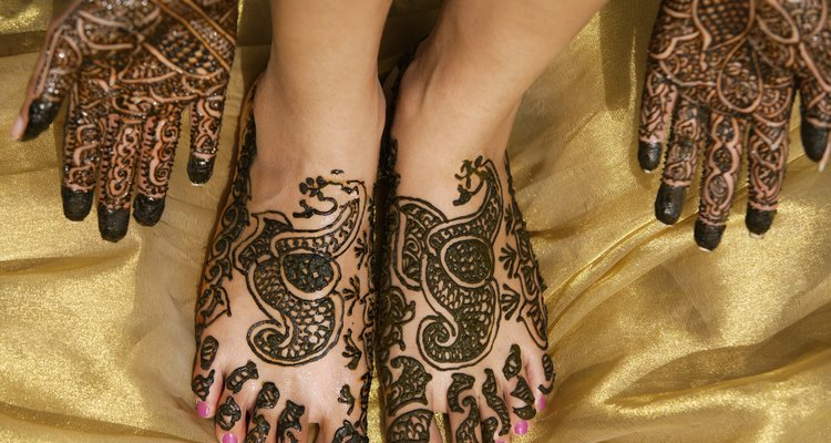 Woman with ornate henna design on feet and hands