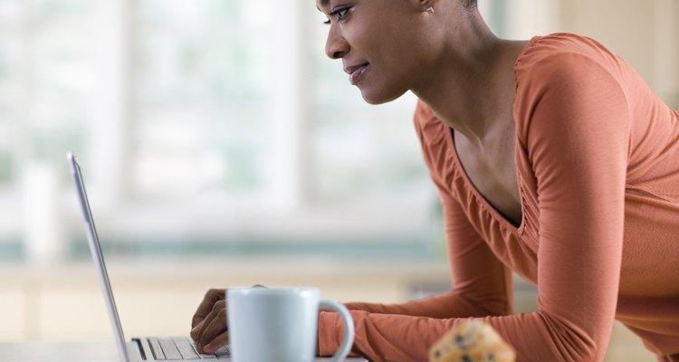 Una mujer registra sus opciones de alimentos en una computadora portátil en la cocina.