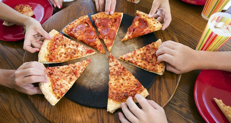 Hands taking slices of pizza