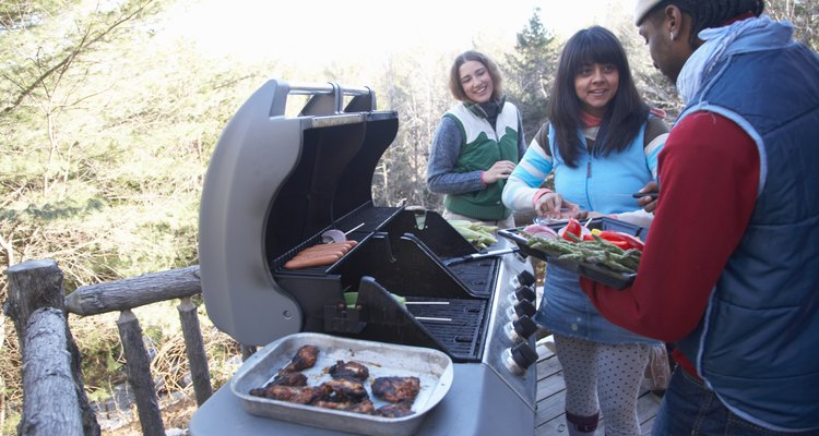 Young people grilling food on porch