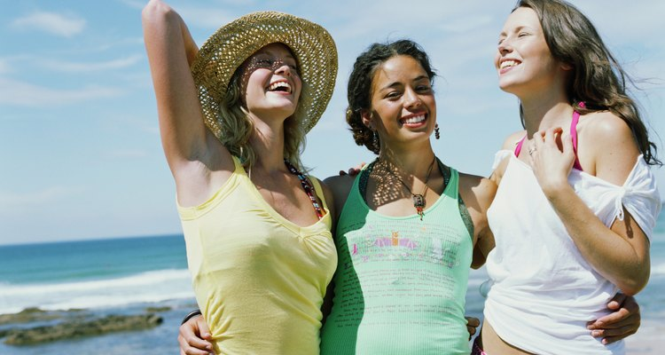 Three women arm in arm on beach, smiling, portrait of woman in centre