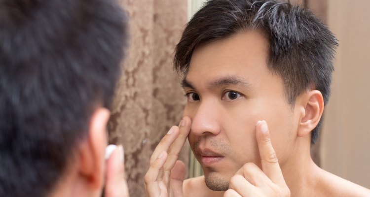 Mirror reflection of a young asian handsome man applying facial