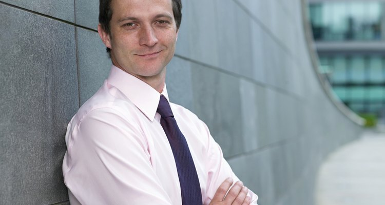 Businessman leaning against wall, arms folded, smiling, portrait