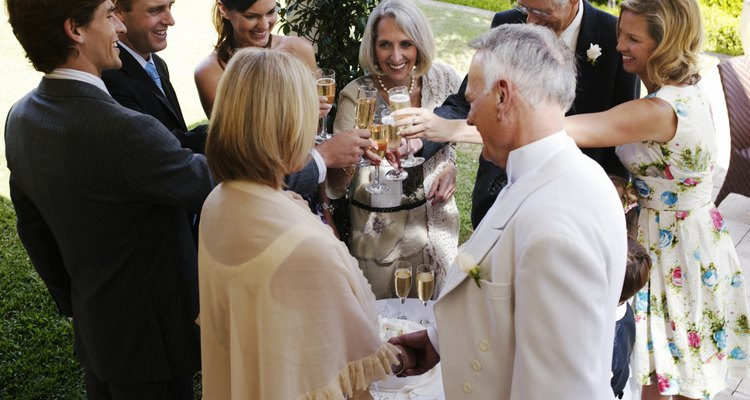 Bride and groom toasting with wedding guests, smiling