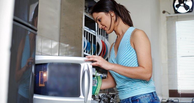 Mujer mirando el microondas.