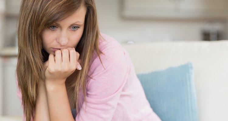 Una mujer triste reflexiona en el sofá.