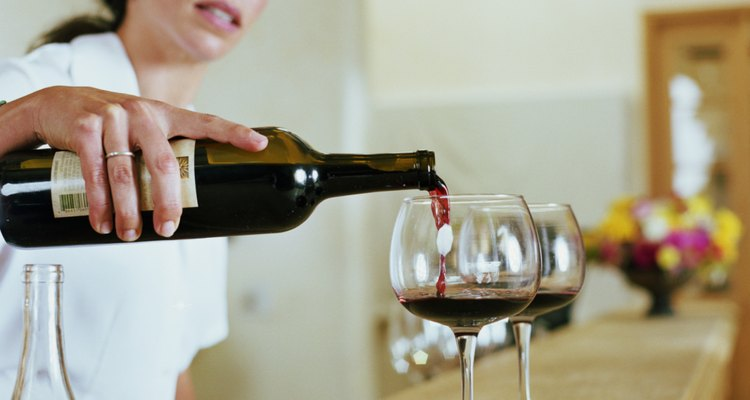 Un camarero de bar sirviendo dos copas de vino tinto en un bar.
