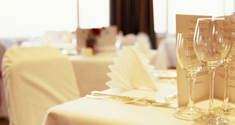 Crea decoraciones para una mesa de boda impresionante con servilletas dobladas elegantemente.