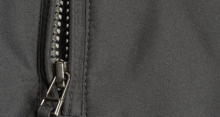 Black polyester twill fabric texture background, open jacket zipper closeup