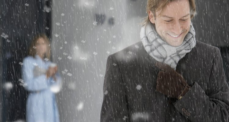 Man leaving house in snow, smiling, woman standing on doorstep