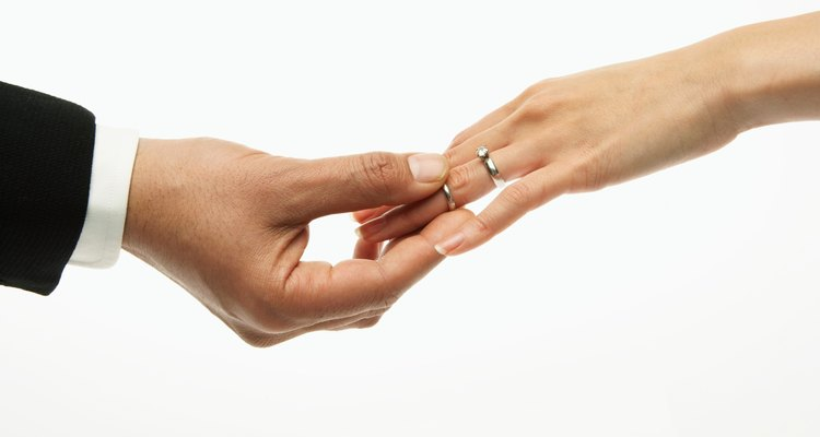 Man placing wedding band on woman's hand (focus on hands)